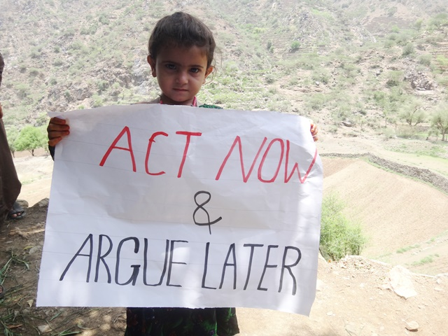 "Une fille tient une pancarte ""Act now & argue later"""